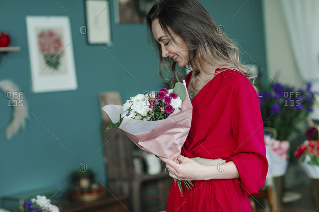 Smiling woman with a bouquet of flowers in a flower shop
