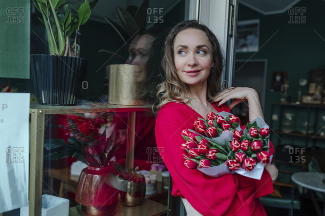 Smiling woman with a bouquet of flowers at the window in a flower shop
