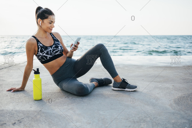 Smiling young woman using smart phone after exercising on promenade