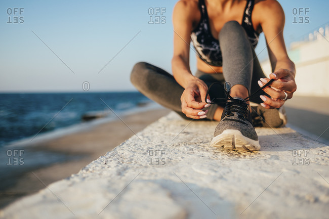 Low section of young woman tying shoelace on promenade