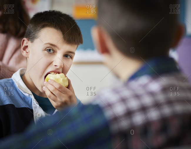 Boy in a classroom during break time eating an apple