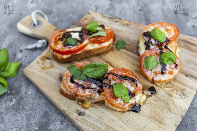 Gratinated baguette slices with tomatoes-mozzarella cheese and basil