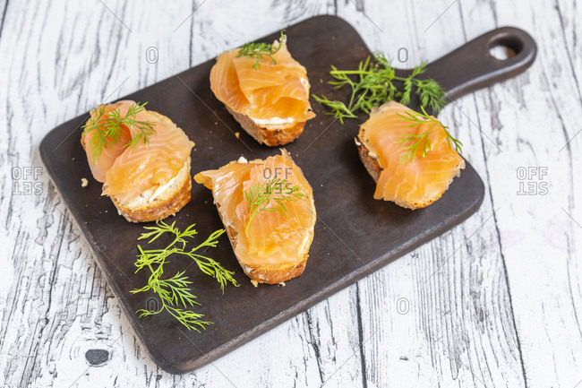 Baguette slices with dill and salmon meat on wooden cutting board