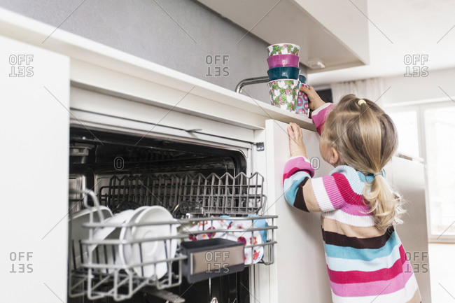 Daughter clearing dishes from the dishwasher
