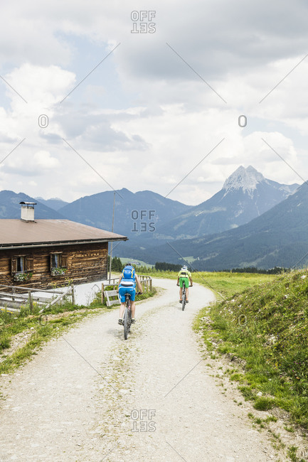 Couple mountain biking on gravel path in the mountains- Achenkirch- Austria