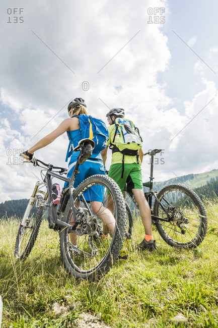 Couple pushing mountain bikes on a meadow in the mountains- Achenkirch- Austria