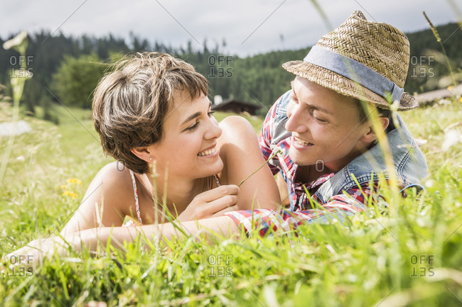 Happy couple lying on a meadow in the mountains- Achenkirch- Austria