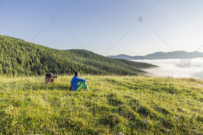 Man and woman with camera on a meadow in the mountains- Achenkirch- Austria