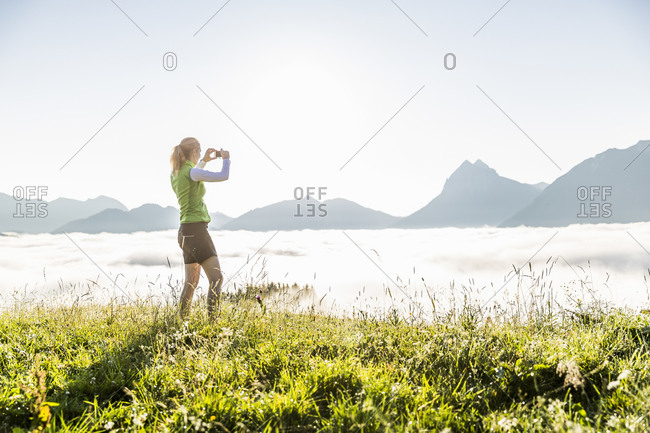 Woman taking a smartphone picture on a meadow in the mountains- Achenkirch- Austria