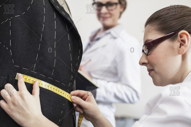 Seamstress measuring bespoke suit jacket