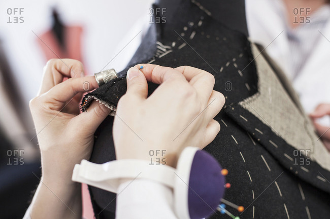 Close-up of seamstress pinning suit jacket