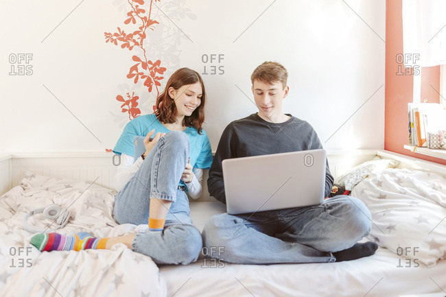 Portrait of teenage couple sitting together on bed learning with laptop