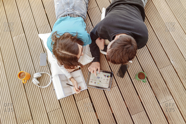 Teenage couple lying on terrace learning together with digital tablet