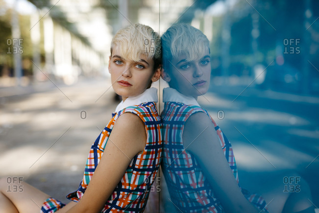 Portrait of female teenager wearing colorful dress mirrored in glass pane