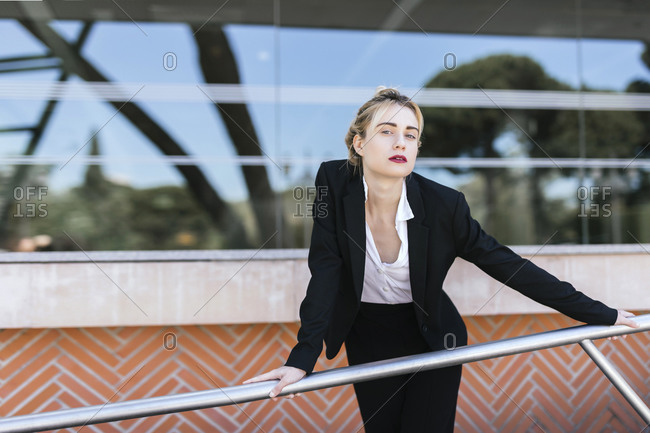 Portrait of young businesswoman wearing black pantsuit standing in front of an office building