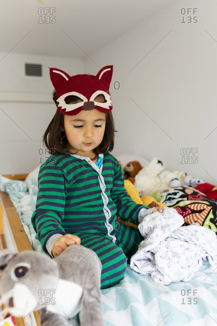 Portrait of little girl with fox mask crouching on bunk bed at home