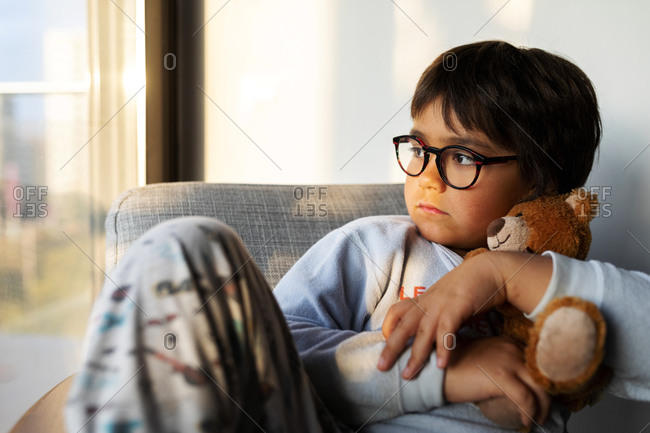 Portrait of serious boy with teddy bear sitting on armchair at home looking out of window