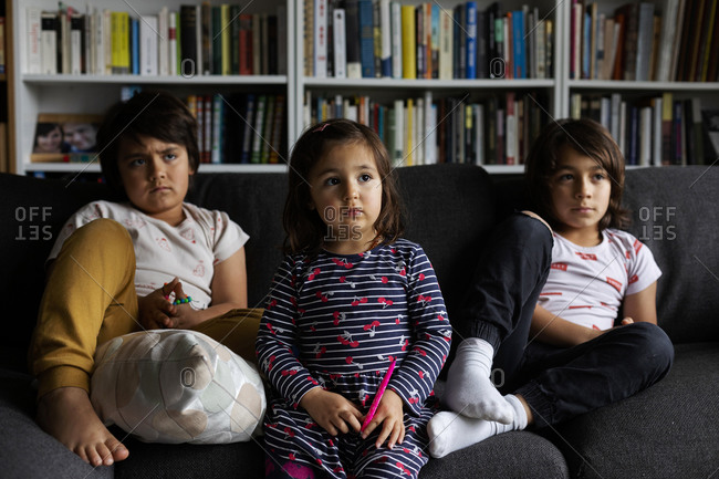 Cute siblings watching TV while sitting on sofa against bookshelf in living room at home