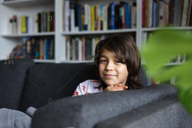 Portrait of smiling boy sitting on sofa against bookshelf in living room at home