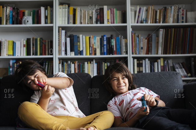 Siblings playing video game while sitting on sofa against bookshelf in living room at home