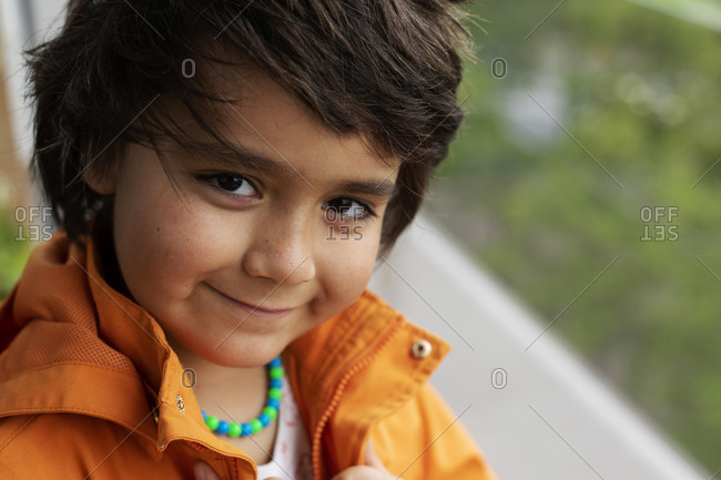 Close-up of portrait of smiling elementary boy wearing orange jacket while standing at back yard