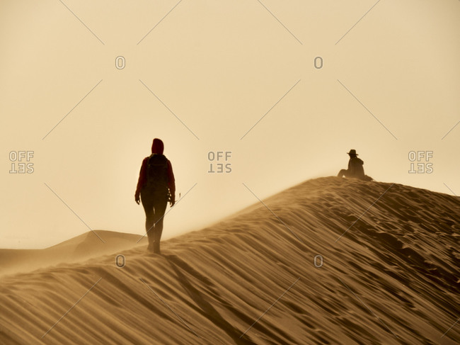 Woman walking on the ridge of a dune in the desert- Walvis Bay- Namibia