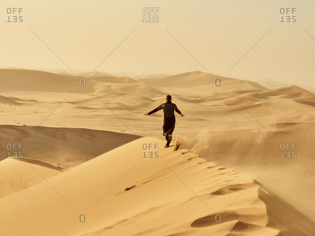 Man running on a dune in the desert- Dune 7- Walvis Bay- Namibia