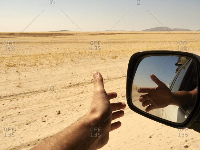 Reflection in the rear view mirror of a man's hand outside the window while driving in the desert- Sossusvlei- Namibia.