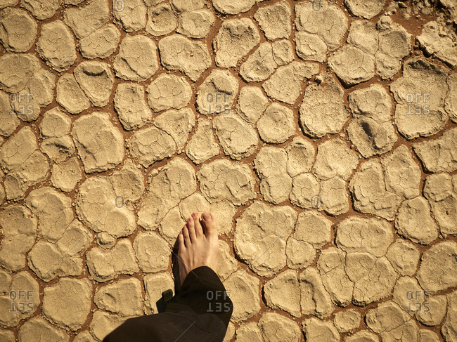 Man's foot on the cracked salt pan floor- Deadvlei- Namibia