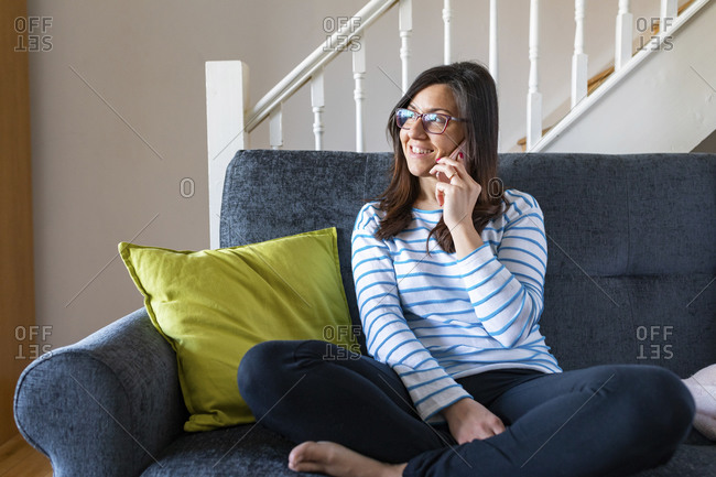 Woman talking on the phone and sitting on sofa at home