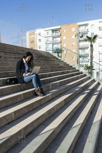 Young businesswoman sitting on stairs outdoors using laptop