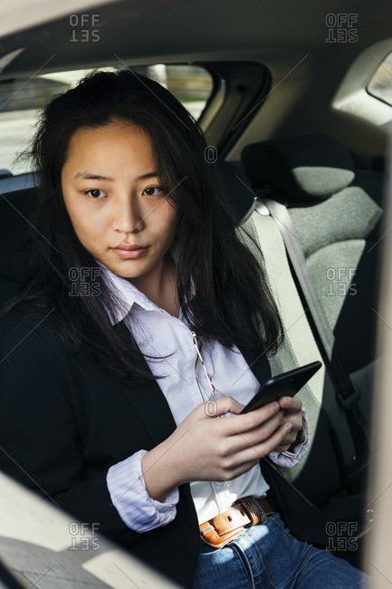 Portrait of pensive businesswoman with mobile phone sitting in a car looking at distance
