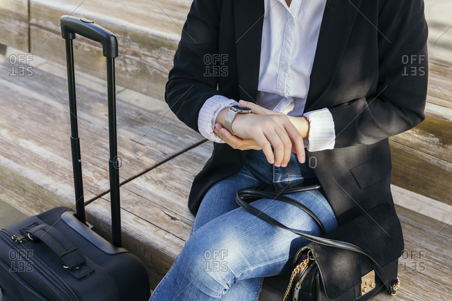 Crop view of young businesswoman with handbag and trolley bag sitting on bench outdoors checking the time