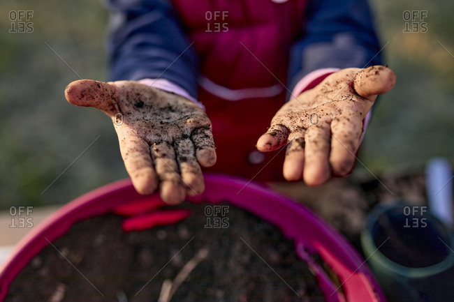 Close-up of girl showing her dirty hands from gardening