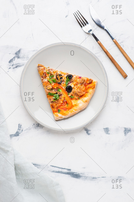 Overhead view of fresh sliced pizza with cheese, tuna and olives