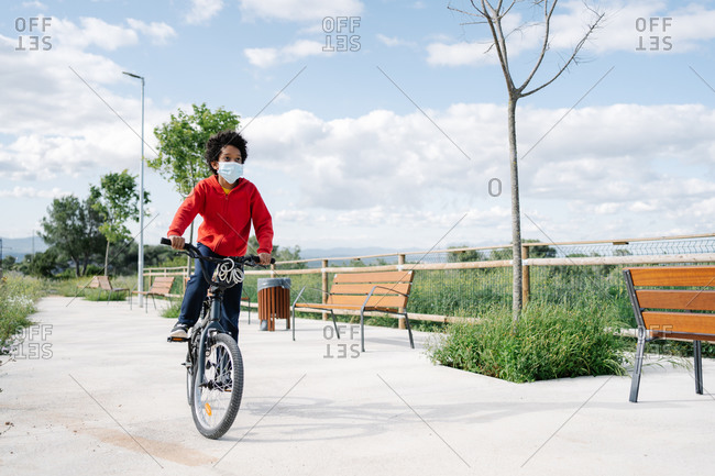 Black boy wearing face mask riding a bike outdoors