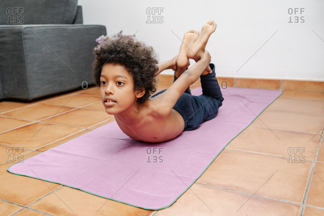 Black boy lying down doing bow pose on the floor at home