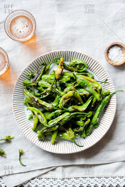 Fried shishito peppers (padron peppers) on a plate with glasses of beer, top view