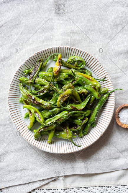 Fried shishito peppers (padron peppers) on a plate, top view