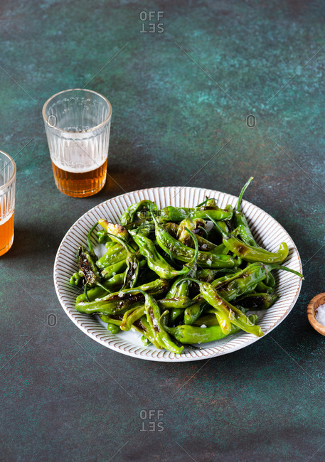 Fried shishito peppers (padron peppers) on a plate with glasses of beer