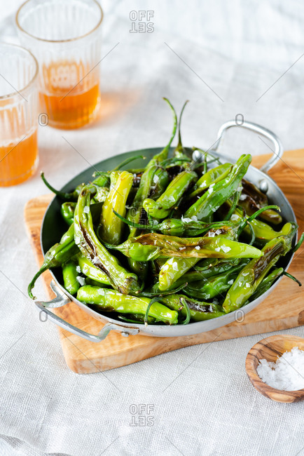 Fried shishito peppers (padron peppers) in vintage skillet with glasses of beer