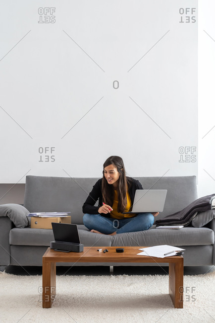 Young woman with laptop and tablet telecommuting on the sofa at her home