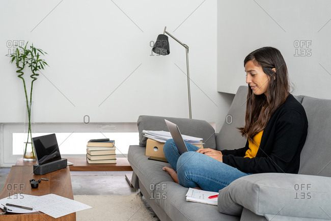 Young woman with laptop telecommuting on the sofa at her home