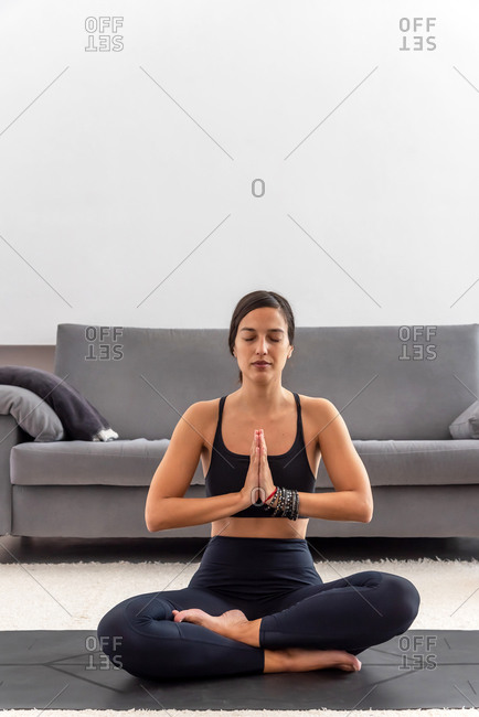 Attractive woman sitting on lotus position with her eyes closed at home