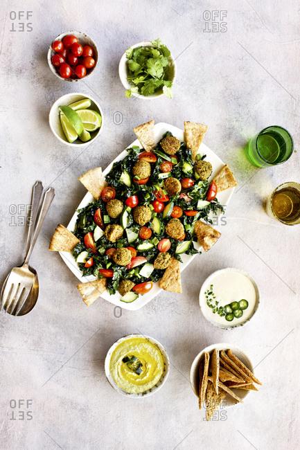 Roasted poblano kale falafel salad with jalapeno tahini sauce on light background