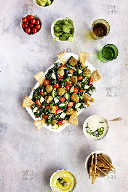 Overhead view of roasted poblano kale falafel salad with jalapeno tahini sauce on light background