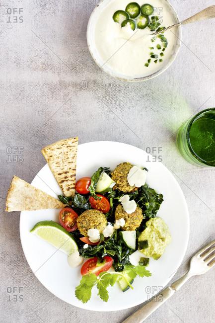 Roasted poblano kale falafel salad with jalapeno tahini sauce served on a plate