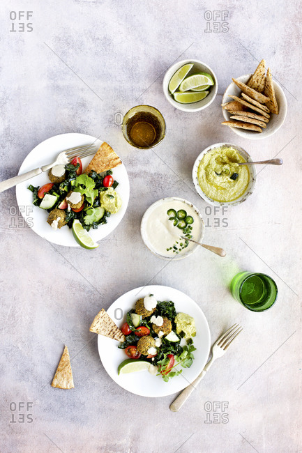 Overhead view of roasted poblano kale falafel salad with jalapeno tahini sauce served on plates