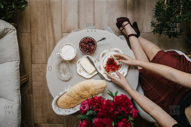 Elegant woman in high heels holding a piece of bread with raspberry jam and butter by fresh peonies