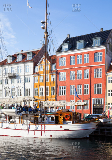 Copenhagen, Denmark - August 21, 2014: A group of people sitting on a boat in the Nyhavn district in Copenhagen with colorful houses in the background